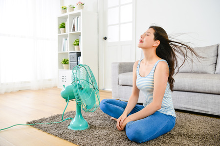 happy elegant woman blowing electric fan in summer day and sitting on living room floor enjoying cool wind to refreshing.