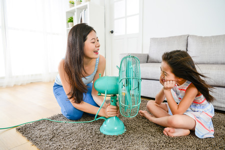 elegant young mother using electric fan helping cute beauty little daughter refreshing with cold wind in summer season at home.