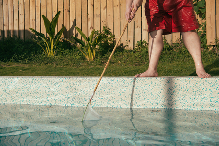 staff using tool cleaning swimming pool to maintain water clean. Stock Photo