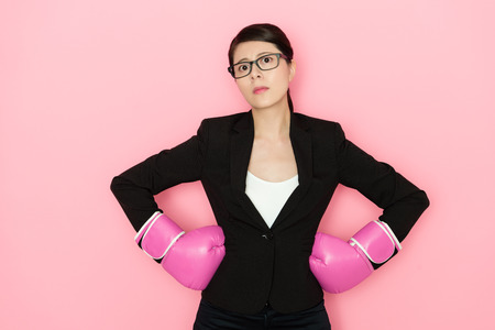 angry professional female manager standing in pink background face to camera and wearing boxing gloves showing seriously emotion.. 스톡 콘텐츠