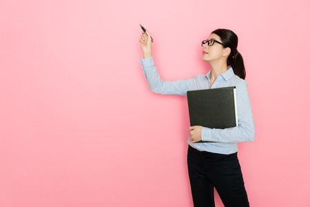 pretty attractive woman office worker using pen writing on simulation screen when she holding work document folder standing in pink background.