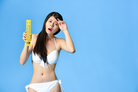Painful unhappy bikini girl presenting thermometer and face to camera showing suffering emotional when she getting headache standing in blue background. Stock Photo