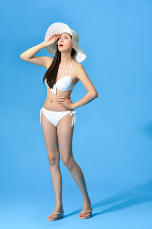 unhappy elegant bikini girl feeling hot during summer season and getting headache painful isolated on blue wall background. full length photo.