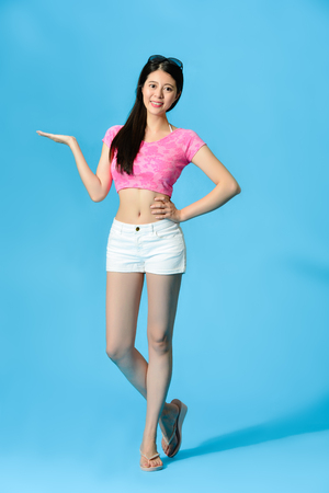 Beautiful young lady wearing summer clothing standing in blue background and face to camera making presenting gesture showing empty area. full length photo.