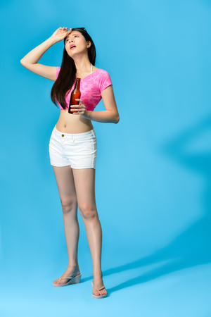 beautiful lovely girl holding beer feeling hot and getting headache painful during summer season isolated on blue background. full length photo.