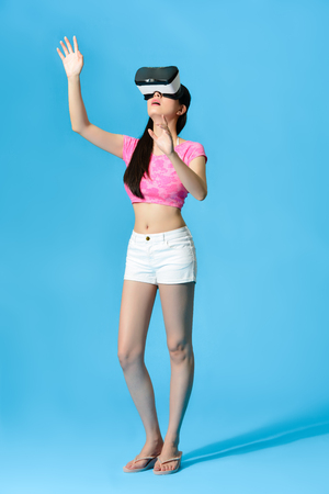 pretty beautiful woman wearing virtual reality device playing 3D game and using hands control isolated on blue background. full length photo.