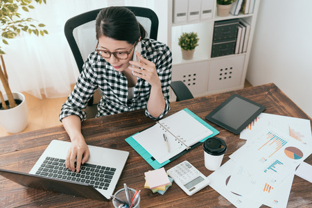 confident attractive business woman using mobile cell phone calling for coworker discussing work plan when she looking at mobile computer working.