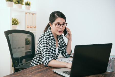 professional beauty girl office worker using mobile smartphone calling for friend chatting relaxing when she watching mobile computer working at home. Stock Photo