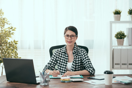 pretty confident female business worker working at home and sitting on workplace room processing company work looking at camera.