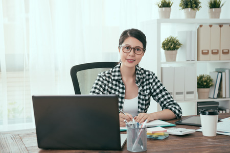 professional young business woman sitting on workplace area looking at camera when she working at home with mobile computer. Reklamní fotografie