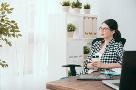 glückliche schöne soho Geschäftsfrau, welche die Kaffeetasse betrachtet das Fenster träumt hält, wenn sie zu Hause im Arbeitsplatz arbeitet.