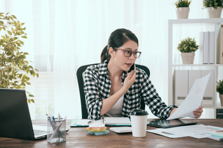 elegant attractive female office worker using mobile cell phone calling for colleague discussing work plan when she working at home and browsing company document.