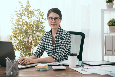 confident happy female office worker doing company work at home and looking at camera smiling.