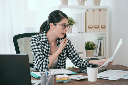 young beautiful female company manager looking at document and using mobile smartphone calling for client discussing cooperation case. Stock Photo
