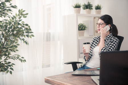 professional young female office worker using mobile cell phone calling for friend chatting when she finished work at home sitting on workplace looking at window relaxing.