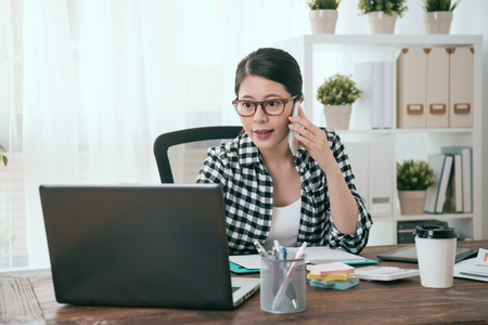 happy attractive female business worker using mobile laptop working at home and looking at file information using mobile cell phone calling for partner discussing plan. Stock Photo