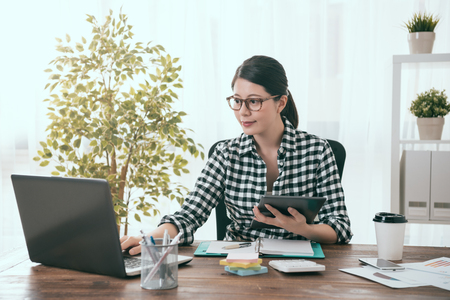 elegant beauty girl business worker holding mobile digital tablet working and connecting laptop to transport work document.