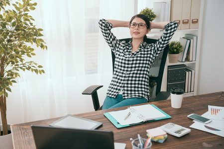 pretty attractive business woman manager lying down on office chair and looking at air daydreaming thinking company work plan.
