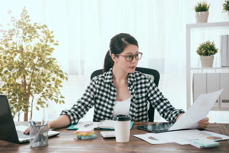 attractive pretty business woman using mobile computer working at home and looking at company marketing analysis document.