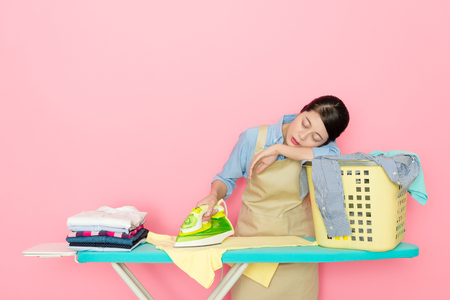 attractive elegant woman worker standing in pink background ironing feeling tired and sleeping on laundry basket resting.