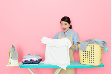cheerful pretty female houseworker looking at white clothing discovering dirt cleaned feeling surprised when she standing in pink background ironing. Stock fotó