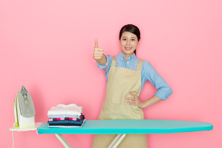 Happy beautiful female house worker showing thumb up gesture looking at camera when she finished ironing all family clothing isolated on pink background.