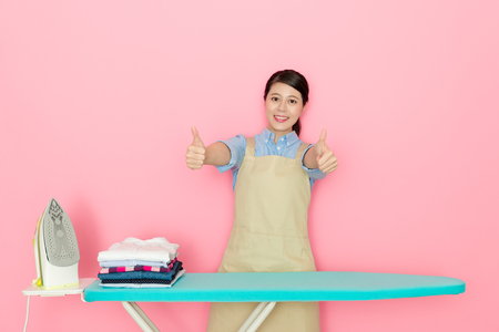 Beautiful happy housewife finished ironing all family clothing face to camera smiling and showing thumb up gesture isolated on pink background.