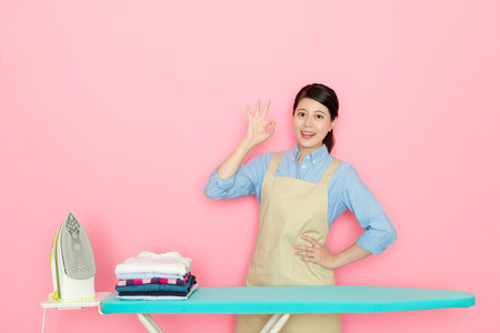 confident young female housekeeper showing ok gesture looking at camera when she finished ironing work isolated on pink background.
