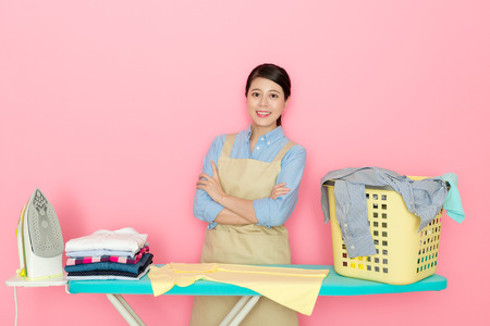 happy beautiful housekeeper woman hands crossed looking at camera smiling when she preparing tool to iron family clothes isolated on pink background.