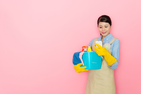 smiling pretty woman houseworker using mobile smartphone searching online information and booking house cleaning service isolated on pink background.