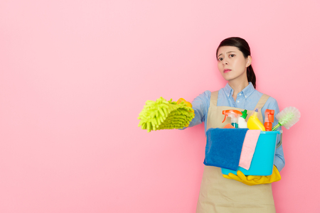 seriously attractive housewife using feather duster tool pointing camera and holding many cleaning equipment standing in pink background.