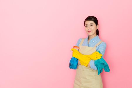 zelfverzekerde jonge huis schoonmaak service werknemer vrouw met doek met wasmiddel staande in roze achtergrond. Stockfoto