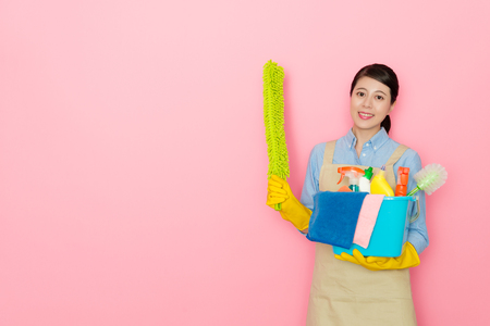 confident beauty female houseworker holding cleaning tool looking at camera and showing green feather duster standing in pink background. Banco de Imagens