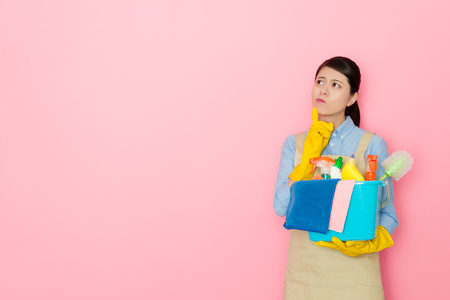 attractive pretty female cleaner worker carrying washing tool standing in pink background and looking at air thinking how to solve clean problem.