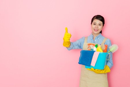 happy young female housekeeper showing thumb up gesture face to camera smiling and holding all cleaning tool standing in pink background.
