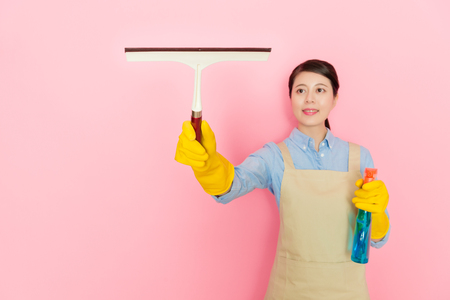 young beautiful lady housekeeper standing in pink background washing window and using glass wiper cleaning detergent foam.