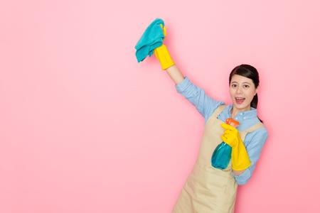 cheerful elegant housewife celebrating finished housekeeping isolated on pink background. Stock Photo