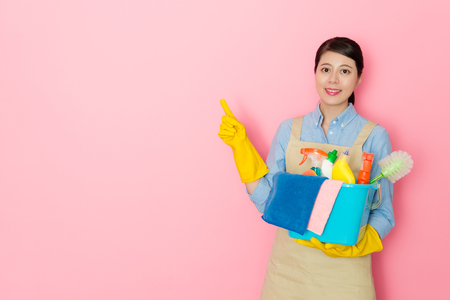elegant professional housework service woman pointing empty area face to camera and holding many cleaning tool standing in pink background.
