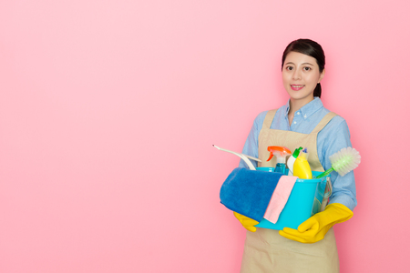 beautiful pretty housekeeper woman holding cleaning tool standing in pink background preparing to sweep house and looking at camera smiling. Stock Photo