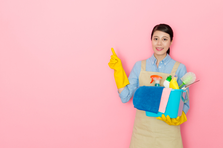 attractive beauty housewife carrying many washing tool ready to clan house and pointing air when she having good idea about work isolated on pink background.