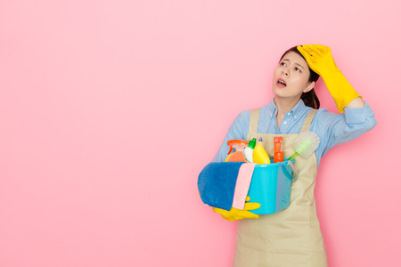 pretty elegant housewife cleaning house long time feeling tired and getting headache painful isolated on pink background.