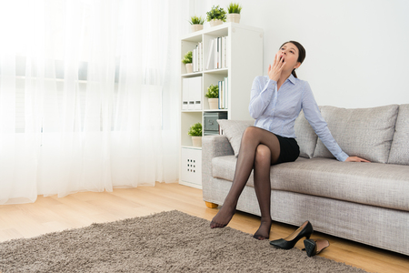 かわいい美少女サラリーマンは、ソファの上に座って、疲れたあくびを感じて家に戻って仕事を終えました。 写真素材 - 94531790