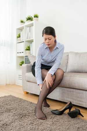 young beauty lady business worker wearing high heel shoes working long time feeling calf painful and sitting on sofa relaxing when she after work. Stock Photo