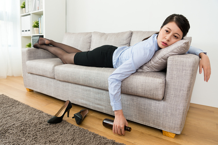 attractive beauty girl worker drunk lying down on sofa resting when she getting layoff information feeling sadness and back to home drinking beer. Stock Photo