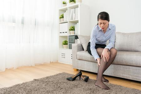 아름 다운 예쁜 비즈니스 여자 집에 다시 작업 후 휴식 및 느낌 송아지 고통스러운 이륙 높은 휴식 신발 소파 휴식에 앉아.