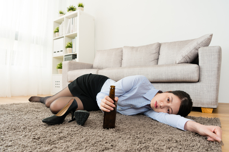 unhappy young female office worker lying down on living room floor resting when she losing work and back to home drinking beer.