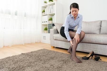 エレガントな魅力的な女性サラリーマンは、ソファのソファに座って自宅に帰るとふくらはぎが痛いと感じ、リラックスしてハイヒールの靴を脱ぐ 写真素材