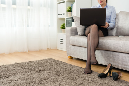 professional young business woman after work back to home take off high heel shoes relaxing and sitting on sofa using mobile laptop working. Banque d'images