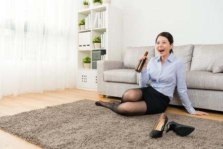 幸せなエレガントな女性オフィスマネージャーは、彼女が家に帰った後にリラックスするためにテレビを見て、ビールを飲んで床に座っています。