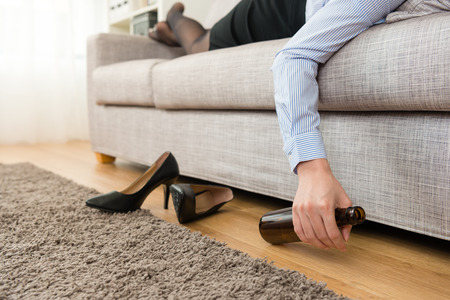 closeup photo of business woman take off high heel shoes lying down on sofa and drinking beer.